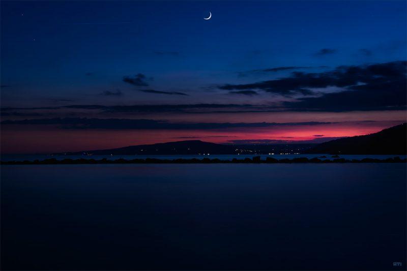 Цветна фотография на залез с луна и звезди